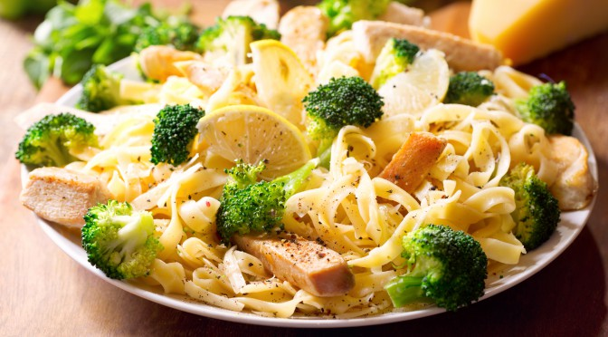 plate of pasta with chicken and broccoli on wooden table